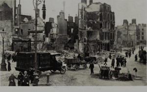 Photograph, shows a Jacob's lorry making its way through the rubble after the 1916 Easter Rising.