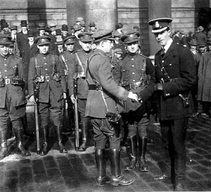The handover of the Bank Of Ireland. Shaking hands are Deputy Commisioner Barret and Captain Haylet. The officer standing in between them is the bold Vinny Byrne of the Squad.